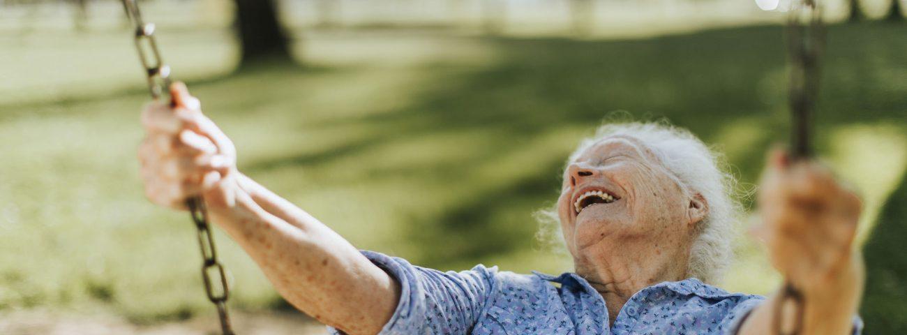 Alte fröhliche Frau beim Schaukeln im Garten