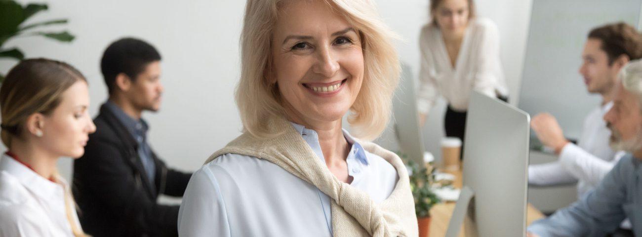 Im Vordergrund ist eine blonde, freundlich lächelnde Frau mit über den Schultern liegendem hellbrauen Pulli über einer blauen Bluse zu sehen. Im Hintergrund sitzen sich mehrere jüngere Männer und Frauen an Bildschirmen gegenüber und diskutieren miteinander.