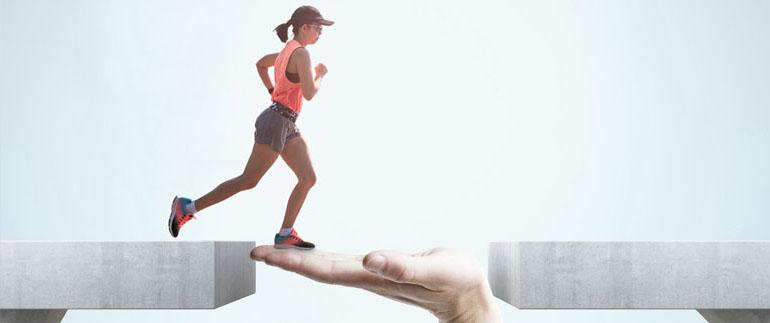 Zu sehen ist eine Grafik, in welcher in der Mitte eine nach oben gewandte flache Hand symbolisch den Abstand zwischen zwei Tischen überbrückt. Von links läuft eine junge Frau im Sportdress über diese lebendige Brücke.