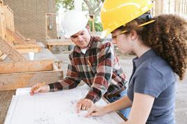 Eine junge Frau mit einem gelben Schutzhelm sowie einem Bleistift hinter dem Ohr lässt sich von einem etwas älteren Mann mit weißem Schutzhelm in einer Werkstatt etwas erläutern.