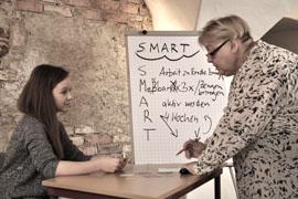 Ein Foto zeigt links eine junge Frau an einem Tisch sitzend. Von rechts ist eine ältere Frau zu sehen, die der Jüngeren etwas erläutert. Im Hintergrund ist ein beschriebenes Flipchart zu sehen.