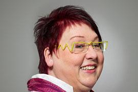 Fröhliche Frau mit kurzen roten Haaren und gelber Brille schaut von links nach rechts.