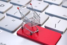 Eine Grafik zeigt eine rote Entertaste auf einer Computertastatur. Auf der roten Taste steht ein winzig kleiner nachgebildeter Einkaufswagen. Die Abbildung symbolisiert den SHOP.