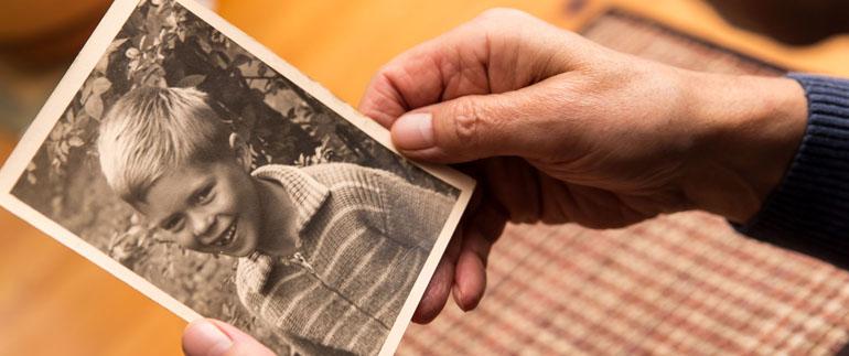 Zu sehen ist die rechte Hand einer offensichtlich älteren Person, die ein altes Foto von einem 6-bis 8jährigen Jungen zum Betrachten hält