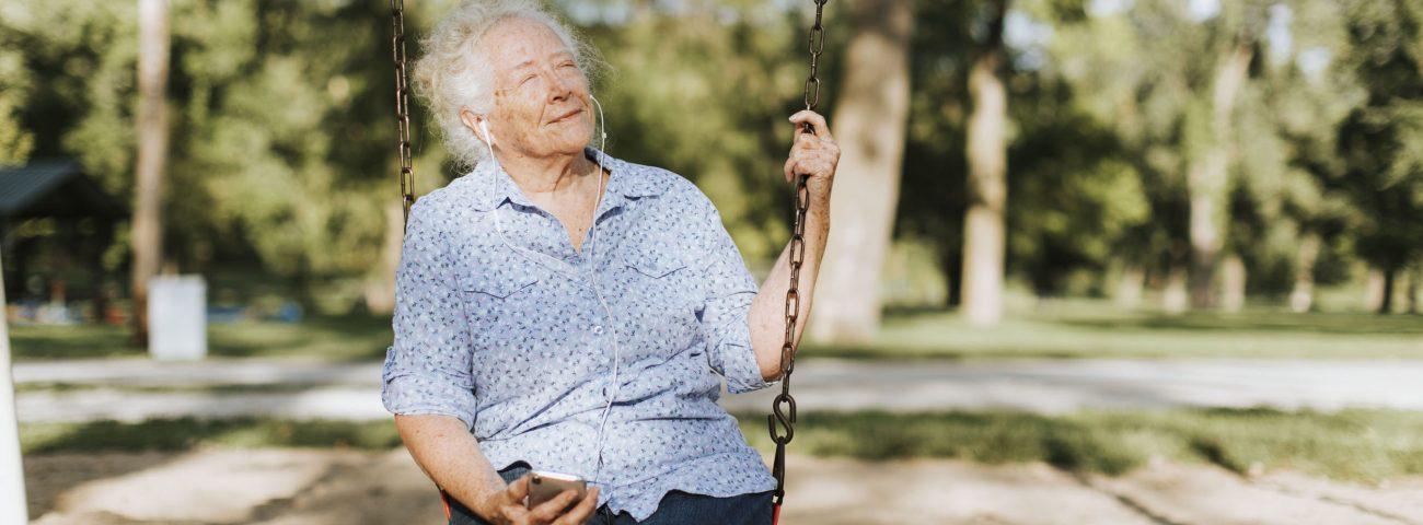 Alte Frau sitzt mit geschlossenen Augen auf einer Kinderschaukel im Park und lässt ihr Gesicht von der Sonne bescheinen. Sie hält in der rechten Hand ihr Handy und hört etwas über Kopfhörer.