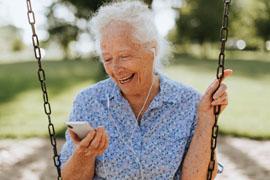 Alte Frau sitzt auf einer Kinderschaukel im Park. Sie hält in der rechten Hand ihr Handy und hört etwas über Kopfhörer.